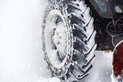 雪清洁 拖拉机在大雪以后扫清道路 接近轮胎 吹雪机平地机清除积雪的路 免版税库存照片