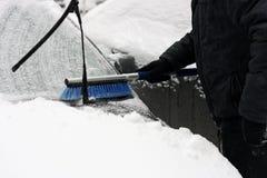 从雪清洗汽车的人 库存图片