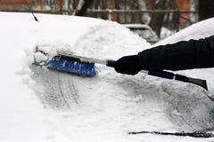从雪清洗汽车的人 免版税库存图片
