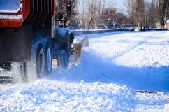 雪犁卡车workiyng在城市公园 库存照片