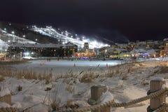 滑雪瑞士山中的牧人小屋倾斜夜光和冰鞋池塘 库存照片
