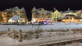 滑雪瑞士山中的牧人小屋村庄光和夜滑冰 免版税库存图片