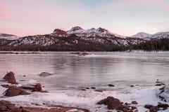 雪用日落颜色加盖了峰顶 库存照片