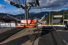 滑雪电缆车的空的驻地与椅子的反对在a的山景 免版税库存图片