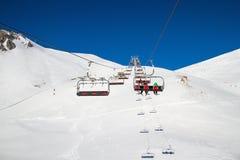 滑雪电缆车运载的滑雪者,挡雪板在一个明亮的晴朗的冬日 免版税图库摄影