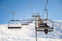 滑雪电缆车,与滑雪者的cablechair在滑雪胜地的一个晴天 免版税库存照片