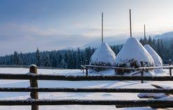 雪的三个干草堆在山冠上 免版税库存照片