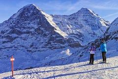 滑雪的两个女孩在冬季体育在瑞士阿尔卑斯依靠 免版税库存照片