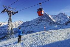 滑雪的人在冬季体育的悬索铁路附近在瑞士Al依靠 免版税库存图片