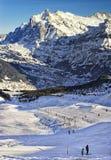 滑雪的人们和雪板临近在冬季体育的悬索铁路 免版税库存照片