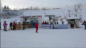 滑雪的人们适应在一个队列的身分推力的能从在滑雪的山退出 股票视频
