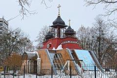雪的大色的基督教会在篱芭后 免版税库存图片