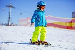 滑雪的小男孩下坡 免版税库存照片