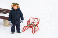 雪的小男孩与他的雪橇 免版税库存照片