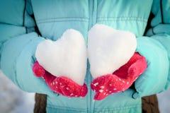 雪的心脏在您的手上,在多彩多姿的手套的棕榈 库存照片