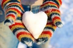 雪的心脏在您的手上,在多彩多姿的手套的棕榈 免版税库存照片