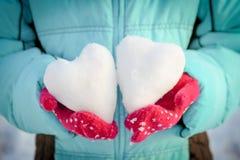 雪的心脏在您的手上,在多彩多姿的手套的棕榈 库存图片