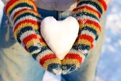 雪的心脏在您的手上,在多彩多姿的手套的棕榈 免版税库存图片