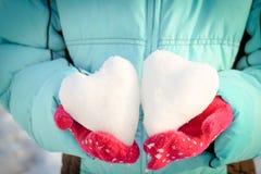 雪的心脏在您的手上,在多彩多姿的手套的棕榈 图库摄影