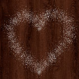 从雪的心脏形状在黑暗的木背景 图库摄影