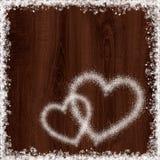 从雪的心脏形状在黑暗的木背景 免版税库存图片