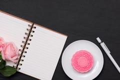 雪皮肤月饼和桃红色花在黑暗的背景 打开没有 库存图片