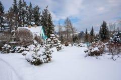 雪盖的冬景花园的美丽的房子 免版税库存照片