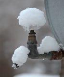 雪盖的室外金属龙头 免版税库存照片