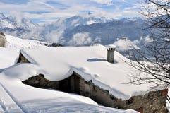 雪盖的瑞士山中的牧人小屋的屋顶 免版税库存图片