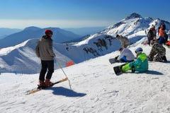 滑雪者和挡雪板前面在滑雪轨道下降 免版税图库摄影