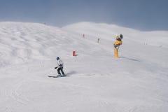 滑雪者和雪大炮 库存照片