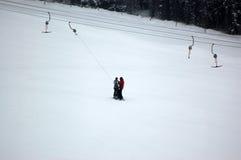 滑雪者和滑雪吊车在滑雪区域 免版税库存照片