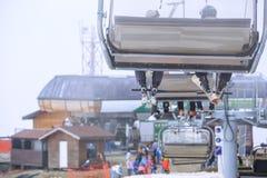 滑雪者在一辆空中览绳椅子滑雪电缆车的`腿在多云多雪的冬天山关闭  库存图片