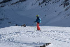滑雪者观察方式向前到在遥远的locat的积雪的谷里 库存照片