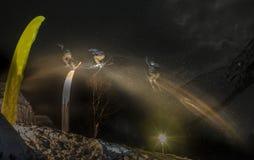 滑雪者跳跃的自由式讨便宜者在雪的晚上 迷离曝光 库存照片