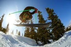滑雪者从在滑雪胜地的一个跳板跳 免版税库存照片