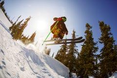滑雪者从在滑雪胜地的一个跳板跳 免版税库存图片