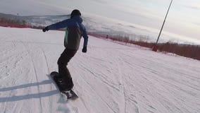 滑雪胜地的挡雪板 运动员在雪的雪板切开在晴朗的天气 人在a打扮 股票录像