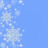 雪花与蓝色背景毗邻 库存照片