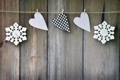 雪花和手工制造心脏在老木背景 免版税库存照片