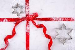 雪花在红色丝带包裹的大理石酥皮点心板的曲奇饼切削刀拂去了灰尘用糖果商糖 免版税库存照片