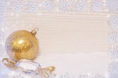 雪花框架,金黄圣诞节玩具球和糖果在雪、光木背景和拷贝空间说谎 免版税库存图片
