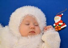 雪花的一套新年的衣服的睡觉的婴孩与一个玩具父亲弗罗斯特的蓝色背景的 免版税库存图片