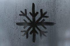 雪花的图象画与一个misted玻璃窗的表面上的一个手指 冷淡的天气 库存图片