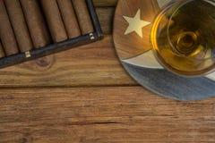 雪茄和兰姆酒或者酒精在桌上 免版税图库摄影