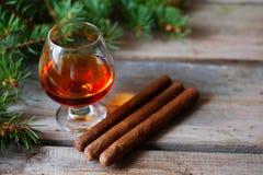 雪茄和科涅克白兰地在一张老木桌上 免版税库存照片