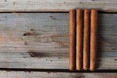 雪茄和科涅克白兰地在一张老木桌上 免版税库存图片