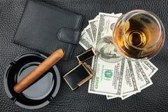 雪茄,烟灰缸,打火机,金钱,钱包,在真正leathe的玻璃 免版税图库摄影