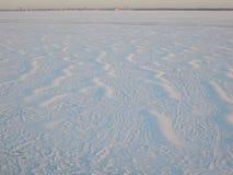 雪表面由在冻河的风创造了 免版税库存照片