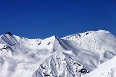 滑雪道多雪的倾斜和蓝色清楚的天空 免版税库存照片